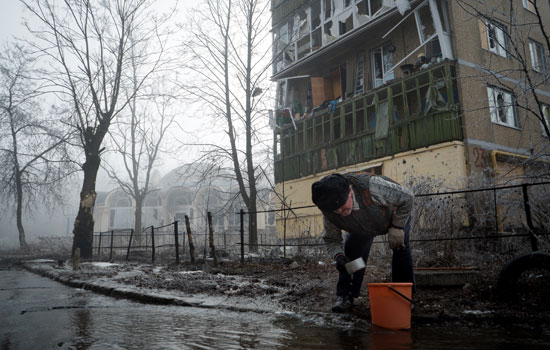 A resident collecting water from a broken water pipe in the ...