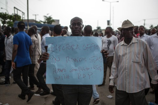 An All Progressives Congress (APC) party supporter holds a sign as others march towards the Independent National Electoral Commission Office in Port Harcourt during a demonstration calling for the cancellation of the presidential election in the Rivers State on March 29, 2015. Thousands of supporters of Nigeria's main opposition party demonstrated in the southern state of Rivers, calling for the cancellation of elections locally because of alleged irregularities. AFP PHOTO / FLORIAN PLAUCHEUR