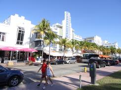 image source AFP / Diego Urdaneta A couple walk down Collins Avenue in the Art Déco district of Miami Beach, Florida