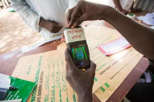 An election official uses an electronic machine to register voters crowding a polling station set up under a tree on the outskirt of Kano during the presidential elections on March 28, 2015. Voting began in Nigeria's general election but delays were reported countrywide because of technical problems in accrediting electors. There was a mixed picture across the country, with people at some polling units reporting no problems in casting their ballot from 1230 GMT but others still waiting for their identities to be checked. AFP PHOTO/TOM SAATER