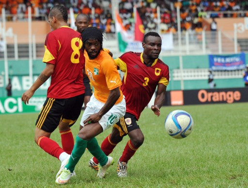 Angola's Carlos Gomes (L) and team mate Osvaldo Paulo Dinis (R) vies for the ball against Ivory Coast national team player Yao Kouassi Gervais (C) during their friendly match on March 26, 2015, at the Felix Houphouet Boigny stadium in Abijan. Ivory Coast beat Angola 2-0. AFP PHOTO/ SIA KAMBOU