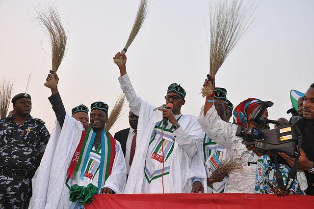 General_Buhari_holding_a_broom_at_a_campign_rally
