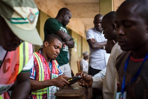 An election official uses a fingerprint reader on a voter at a polling station in Abuja during presidential elections on March 28, 2015. Problems with new technology forced a 24-hour extension to the presidential election in Africa's most populous nation, Nigeria, and renewed Boko Haram violence hit the knife-edge vote. AFP PHOTO / NICHOLE SOBECKI