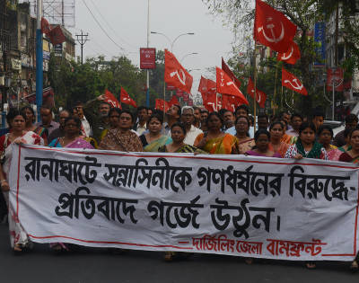 """Indian activists from the Communist Party of India Marxist (CPIM) holds banners reading """"Protest against rape of nun"""" during a rally in Siliguri on March 15, 2015. Prayers were said at churches across India March 15 for an elderly nun who was gang-raped at a convent in an attack that has intensified anger over sexual violence and fuelled fears among beleaguered Christians. The assault on the 71-year-old is the latest in a string of high-profile rapes in India and comes after a spate of attacks on churches that prompted Hindu nationalist Prime Minister Narendra Modi to promise a crackdown on religious violence. AFP PHOTO / Diptendu DUTTA"""