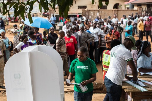 People wait in line to vote at Karu polling station in Abuja during presidential elections on March 28, 2015. Problems with new technology forced a 24-hour extension to the presidential election in Africa's most populous nation, Nigeria, and renewed Boko Haram violence hit the knife-edge vote. AFP PHOTO / NICHOLE SOBECKI