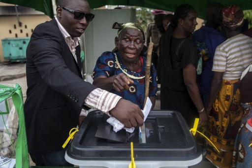 An elderly Nigerian voter is helped to cast her ballot in Otuoke on March 28, 2015. Problems with new technology forced a 24-hour extension to the presidential election in Africa's most populous nation, Nigeria, and renewed Boko Haram violence hit the knife-edge vote. AFP PHOTO/FLORIAN PLAUCHEUR