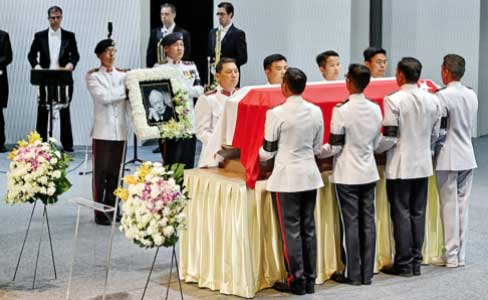 Draped in the national flag, Lee's coffin was taken on a solemn procession through the sodden streets of the tropical city, where crowds of mourners defied the downpour to pay their last respects.