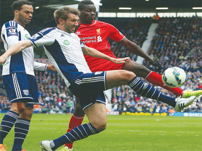 Liverpool's striker, Mario Balotelli (right) vies for the ball with West Bromwich Albion's defender, Gareth McAuley (middle) during the Premiership match at The Hawthorns in West Bromwich, yesterday.         PHOTO: AFP