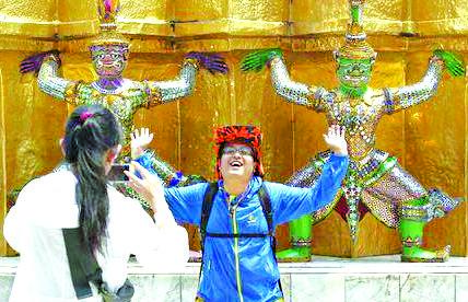 A Chinese tourists strike a pose to statues as they visit the Grand Palace in Bangkok