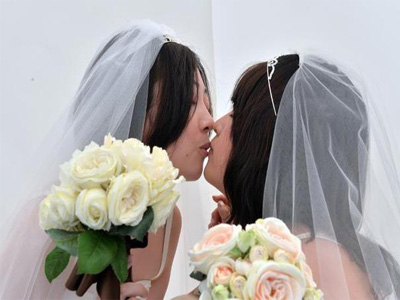 "A lesbian couple kisses as they pose for photos taken by a wedding photo service company in Tokyo before participating in the ""Tokyo Rainbow Pride"" parade in Tokyo on April 27, 2014 ©Yoshikazu Tsuno (AFP/File)"