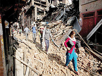 Nepalese residents carry belongings from their destroyed homes as they walk through debris at weekend's earthquake, in Bhaktapur on the outskirts of Kathmandu, Nepal, yesterday. (AP Photo/Niranjan Shrestha)