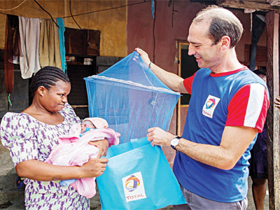 Managing Director, Total Nigeria, Mr. Alexis Vovk (right), presenting a LLIN to a beneficiary in Ibafon community.