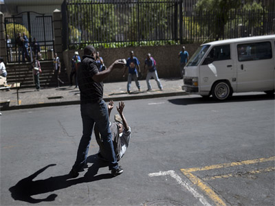 A local taxi driver pelts with stones a man on the ground during a confrontation with foreign nationals in the Johannesburg Central Business District on April 15, 2015. AFP PHOTO/MARCO LONGARI