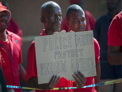 A member of the Economic Freedom Fighters holds a placard as he stands outside the Wynberg Magistrate court, in Alexandra Township, Johannesburg, on April 21, 2015.