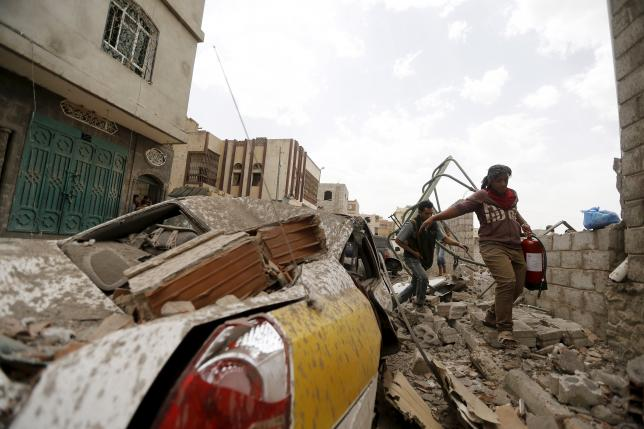 People walk past car damaged by airstrike in Sanaa