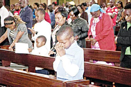 A Kenyan Christian child in prayer as he joined a morning service at Holy Family Basilica, Nairobi, Kenya, yesterday during Easter Sunday when Christians celebrate the resurrection of their Lord, Jesus Christ, according to Scripture after his crucifixion on the cross. Special prayers were held yesterday for the victims of the recent Garissa University Attack, when Al-Shabaab gunmen rampaged through the university in northeastern Kenya on Thursday, killing scores of people. (AP Photo/Sayyid Azim)