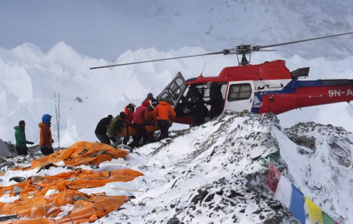 An injured person is loaded onto a rescue helicopter at Everest Base Camp on April 26, 2015, a day after an avalanche triggered by an earthquake devastated the camp. Rescuers in Nepal are searching frantically for survivors of a huge quake on April 25, that killed nearly 2,000, digging through rubble in the devastated capital Kathmandu and airlifting victims of an avalanche at Everest base Camp. The bodies of those who perished lie under orange tents. AFP PHOTO/ROBERTO SCHMIDT