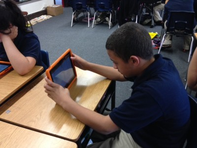a kid using an ipad computer. Photo: Image source cicsbucktown