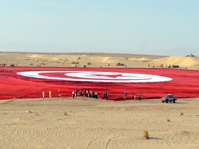 A picture taken on May 2, 2015, shows a giant Tunisian national flag unfurled at Ong Jmel in the southern desert. Tunisians have unfurled a national flag the size of 19 football pitches in a bid to set a Guinness world record and promote patriotism in the face of Islamist extremism. Organisers said that it took 80 kilometres (50 miles) of fabric to make the 104,544 square metre (1,125,302 square foot) flag which weighed in at 12.6 tonnes. AFP PHOTO / SAIF TRABELSI