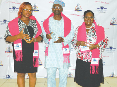 Nkem Okibe of NTA Lagos Channel 10 (left); Mr. Akin Johnson representing the Director, Lagos State Agency for Mass Education, Mrs. Amore Adefola Olufemi; Founder/Medical Director, Ikeja Medical Centre, Dr. (Mrs.) Morayo Apantaku after receiving their awards from ACSEC at the event.