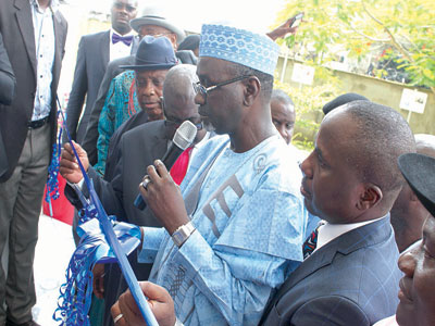 Shekarau, assisted by Azaiki, cutting the tap to commission the project.