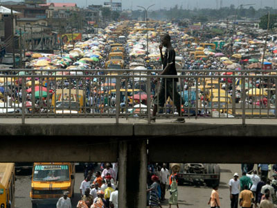 A man walks on a pedestrian bridge overlooking traffic in Lagos, Nigeria. Photo: Blogs