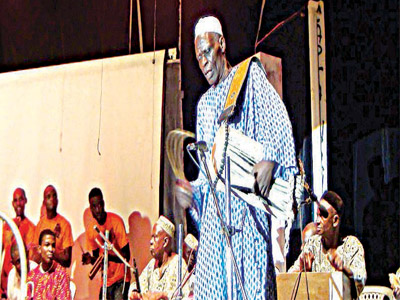 A drummer from the Agidigbo band entertaining the audience with his dexterity on the talking drum