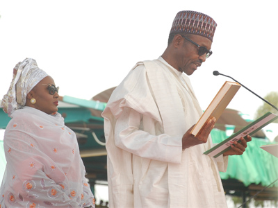 Buhari taking oath of office on Friday with his wife Aisha standing behind him