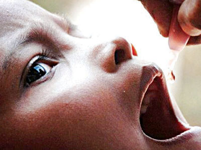 A child receiving drops of oral polio vaccine