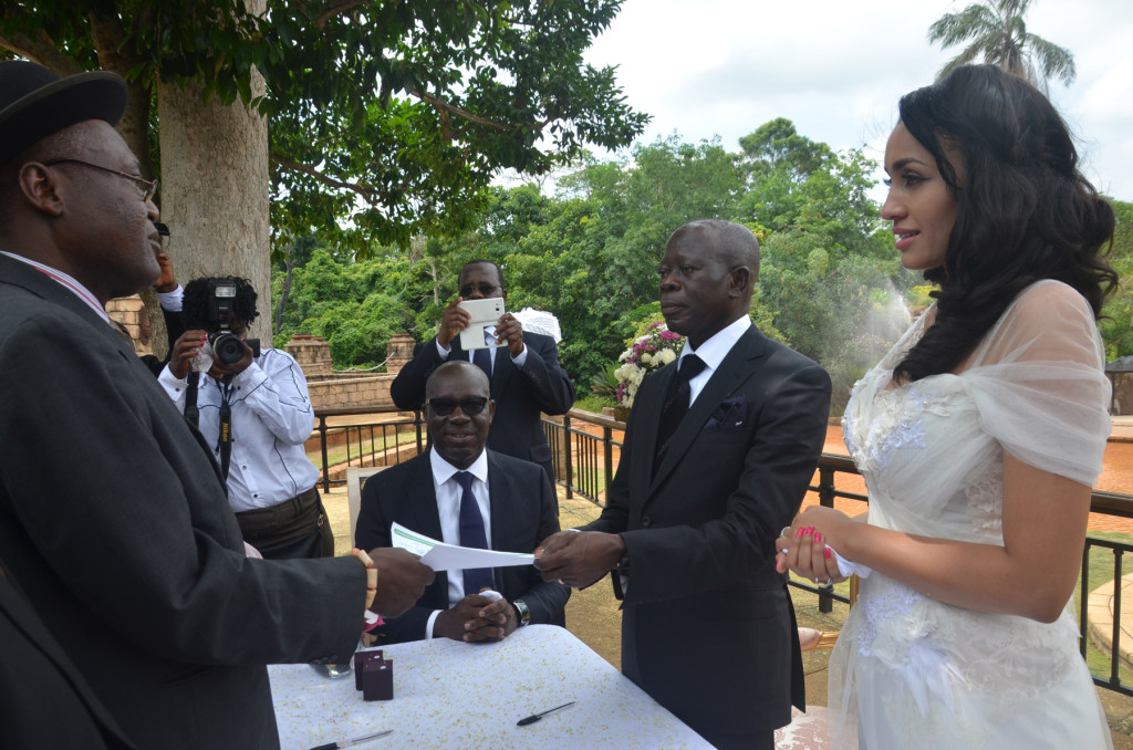 The officiating minister hands the marriage certificate to the Comrade Governor
