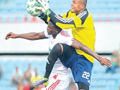 New Super Eagles invitee, Sunshine Stars' goalkeeper, Ikechukwu Ezenwa (right), in an aerial battle with an FC Giwa striker during a recent Glo Premier League game.