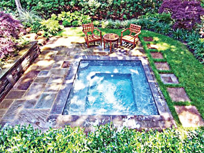 Relaxing getaway, a gunite spa surrounded by blue stone patio and sitting area. The play of light and shadows enhances this private oasis amidst lush plantings
