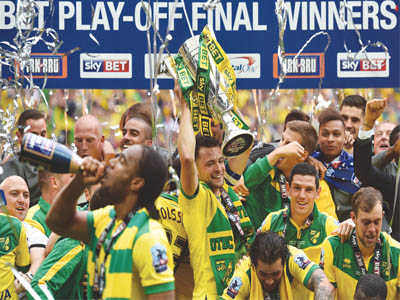 Norwich City's players and officials celebrating the club's return to the English Premiership after their 2-0 defeat of Middlesbrough in the Championship play-off at Wembley… yesterday.        PHOTO: AFP.