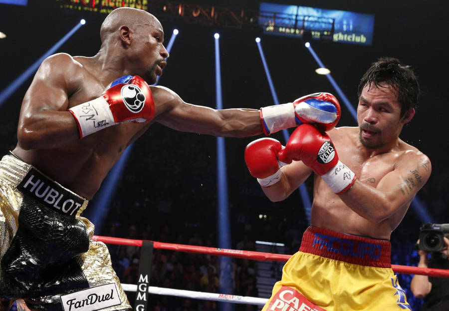 US boxer Floyd Mayweather Jr., (L) punches Manny Pacquiao of the Philippines during their welterweight unification boxing bout at the MGM Grand Garden Arena in Las Vegas, Nevada on May 2, 2015. AFP PHOTO / JOHN GURZINKSI