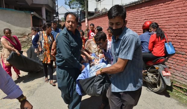 Nepalese patients are carried out of a hospital building as a 7.4 magnitude earthquake hits the country, in Kathmandu on May 12, 2015.   A 7.4-magnitude earthquake hit devastated Nepal, sending terrified residents running into the streets in the capital Kathmandu, according to witnesses and the US Geological Survey.  The quake struck at 12:35pm local time in the Himalayan nation some 83 kilometres (52 miles) east of Kathmandu, more than two weeks after a 7.8-magnitude quake which killed more than 8,000 people.   AFP PHOTO / PRAKASH MATHEMA