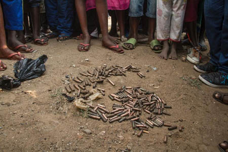 People stand around a cluster of empty cartridges lying on the ground in the Jabe distirct of Bujumbura on June 28, 2015 after a night of intense shooting that saw a young man allegedly killed by police (AFP Photo/Landry Nshimye )