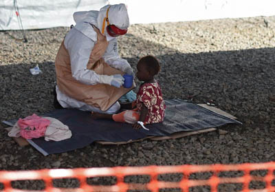 An Ebola health worker wearing protective equipment gives to drink to an Ebola young patient at Kenama treatment center run by the Red cross Society on November 15, 2014 (AFP Photo/Francisco Leong)