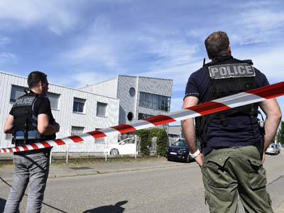 French police officers stand guard near a cordon outside the delivery service company in Chassieu on June 26, 2015, where the victim who was decapitated worked (AFP Photo/Philippe Desmazes)