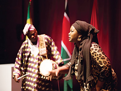 Bikiya Graham-Douglas performing Wait in honour of African women, with the accompaniment of a talking drummer urging her on