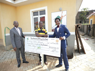 Director, Home Lottery Limited; Mr. Christian Abraham (left), presenting a cheque to Mr. Gabriel Mokogwu, the first winner of a house in the company's ongoing Home Lottery for the perfection of title to the house by Lagos State government while the Managing Director of the company, Mr. Kelvin Otung looks on at the Gold Estate in Alimosho Local Government area of Lagos state8