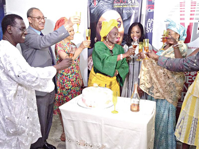 All cheers for the screen matriarch...  Mr. Ben Tomoloju (left); Prof. Pat Utomi; Ajai-Lycett (yellow headgear, middle) and others toasting to her health
