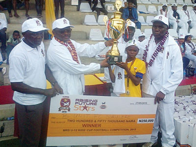 L-R, The MD, MRS oil ,Paul Bissohong presenting the trophy to the Captain of B.Unit boys of Surulere of the 3rd MRS Kids Cup, at the Campos Mini Stadium,Lagos.