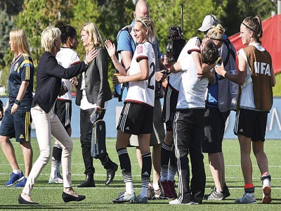Germany's coach Silvia Neid (left) runs to embrace midfielder Lena Goessling (centre) after their 4-1 defeat of Sweden at the FIFA Women's World Cup round of 16.                                                        PHOTO: AFP