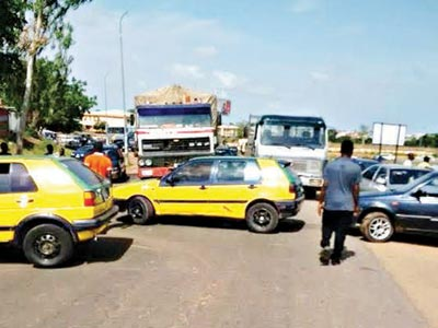 Taxi drivers barricaded the Kaduna-Abuja flyover to protest against alleged police harrassment in Kaduna State
