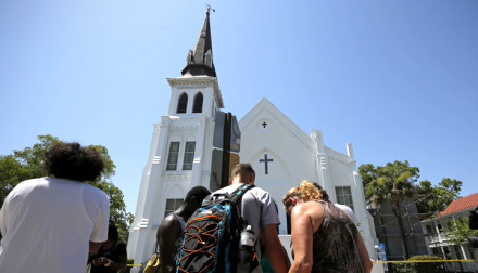 Mourners pay their respects outside Emanuel African Methodist Episcopal Church after the street was re-opened a day after a mass shooting left nine dead during a bible study at the church in Charleston