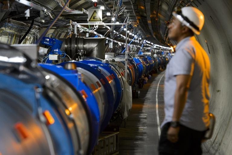 A scientist looks at a section of the Large Hadron Collider (LHC) which was used to prove the existence of the Higgs Boson. PHOTO: BUSINESSINSIDER
