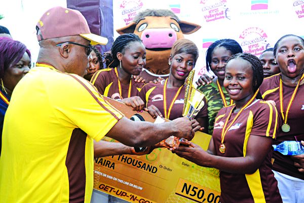 Lagos State NYSC Director, Mr. Cyril Akhanemhe (left), presenting the trophy to the victorious Platoon Six volleyball team.