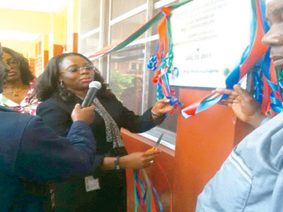 Dr. Effiem Abbah cutting the tape to unveil the plaque at the commissioning of sickbay at Victoria Island Primary Complex in Lagos