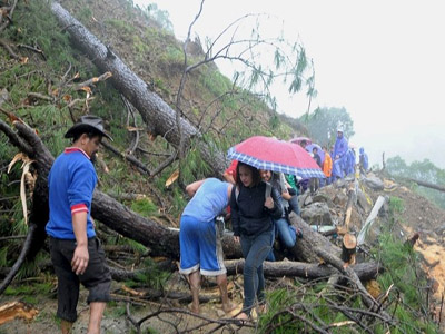 Residents walk on a road covered with debris after landslides brought on by torrential monsoon rains, killed two people in Kennon Road in Benguet province in northern Philippines July 13, 2015.