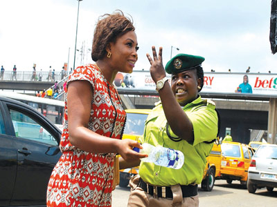 THREE!!! Yeah, but just what could she be saying?  An official of the Lagos State Kick Against Indicipline (KAI) reprimanding a woman who failed to use the pedestrian bridge at Oshodi...last week             PHOTO: AYODELE ADENIRAN